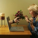 Online dating concept. Hand & Wine Glass Through Laptop Screen